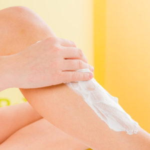 Eine Frau verwendet Enthaarungscreme auf ihrem rechten Bein
