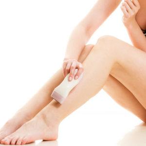Eine Frau verwendet einen Epilierer zur Haarentfernung an ihrem linken Bein