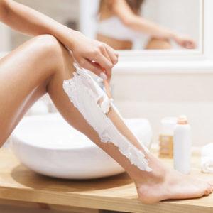 Eine Frau entfernt sich die Haare am Bein mit einem Nassrasierer