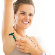 Eine Frau rasiert sich unter der rechten Achsel