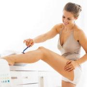 Eine Frau rasiert sich das linke Bein