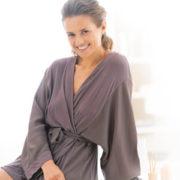 Eine Frau sitzt im Morgenmantel auf der Badewannenkante und lächelt