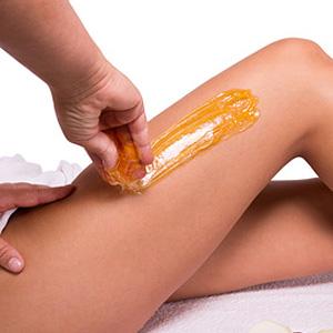 Eine Frau lässt sich ihre Haare am Bein durch Sugaring entfernen