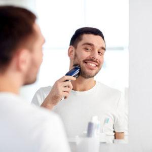 Ein Mann rasiert sich im Gesicht mit einem elektrischen Rasierer