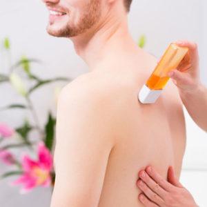 Ein Mann lässt sich seine Haare am Rücken durch Waxing entfernen